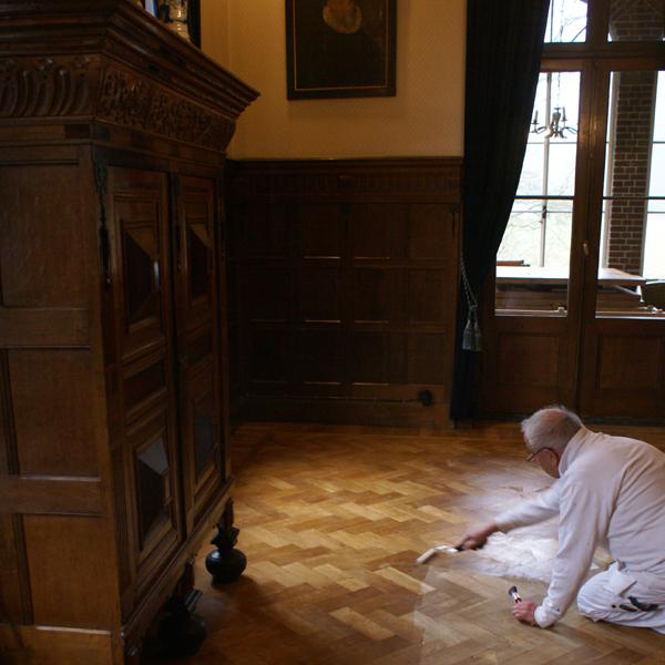 De mooie houten vloer in de sfeervolle 'Huiskamer' van Kasteel Hoekelum in Bennekom wordt door Van Reemst voorzien van een goede nieuwe laklaag en glanst!