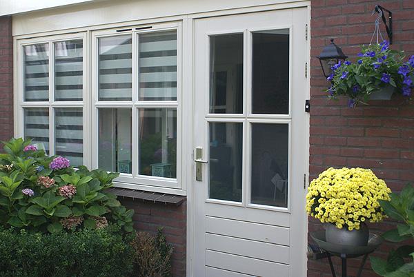 Deur, ramen en houtwerk van een uitbouw van een huis. Recent geschilderd door Van Reemst.