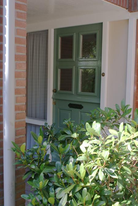 Voordeur in het groen.